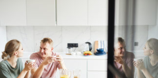 Young restful spouses having brunch and tea in the kitchen